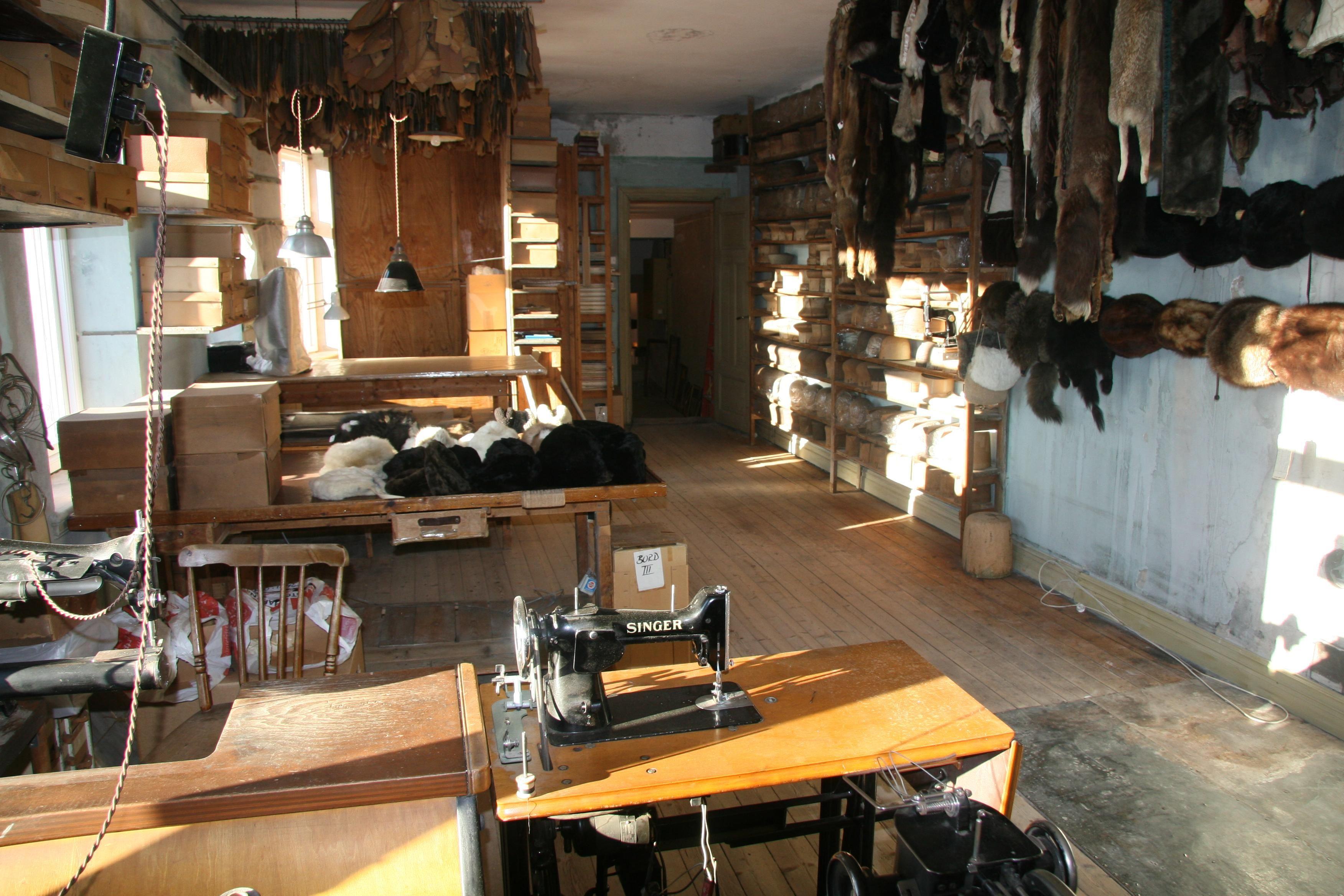 Här hänger pälsverken i rader, i taket trängs mallar till mössor och på väggen är runt 250 olika hattstockar uppradade.