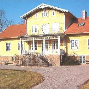 En bild på ett stort gult trähus med rött tegeltak