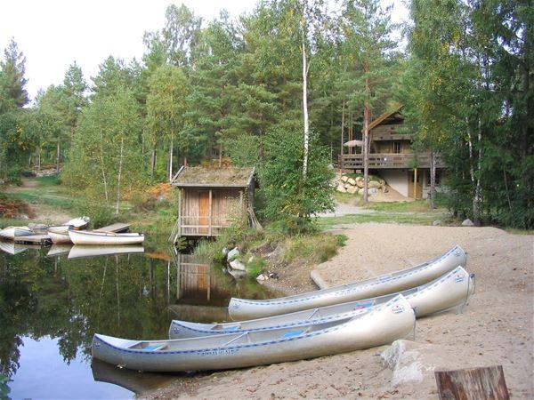 © Hätteboda, Kanoter redo för vattenläge. Bastu och Receptionen i bakgrunden