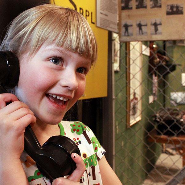Foto: Teknikland,  © Copy: Teknikland, Flicka som håller i en svart telefonlur