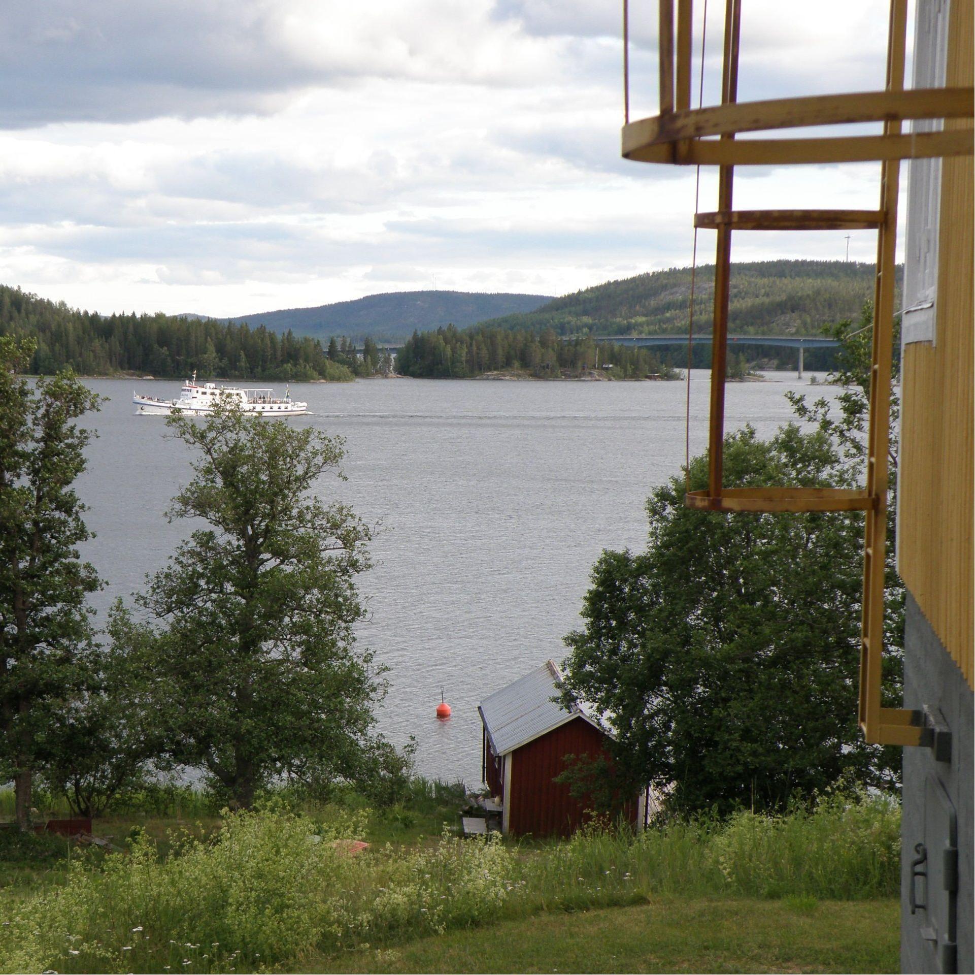 Till höger på bilden syns kortsidan av huvudbyggnaden. Vid vattnet ligger sjöboden där det också finns logi. På fjärden passerar Ådalen III