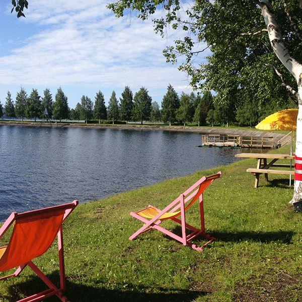 Foto: Visit Östersund, Solstolar på gräset framför vattenkanten
