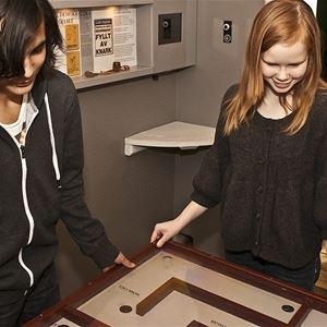 Mats Fallqvist,  © Sveriges Fängelsemuseum, Två ungdomar som spelar ett stort kulspel i en cell.