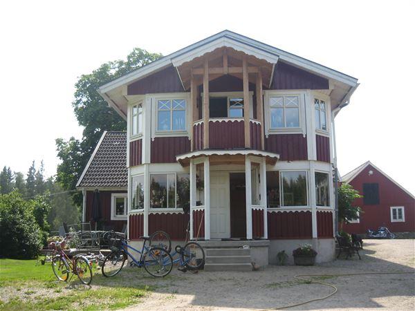 Anna Strömberg, Baksidan av huset där ni äter frukost på verandan med utsikt över ängarna.