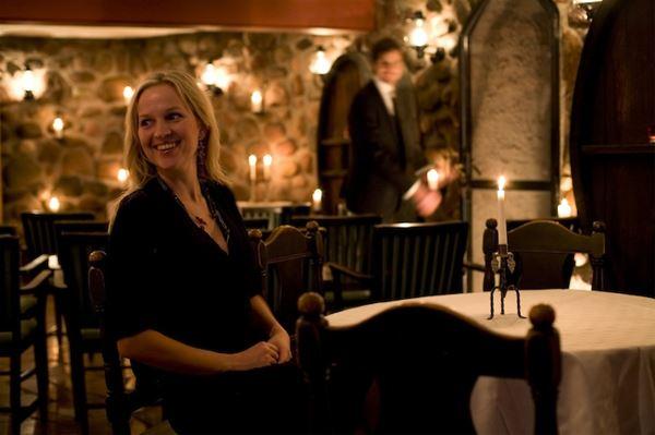 Glad kvinna sitter vid ett bord i restaurangen.