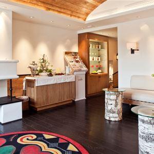 Spats väntrum med öppen spis, soffor och små runda bord.