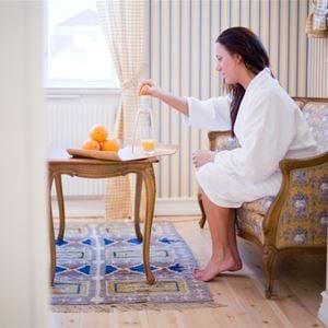 Kvinna som sitter i en soffa i rokoko stil i ett hotellrum. Frukt på bordet.
