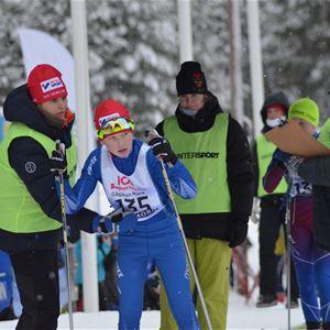 Ungdomar tävlar på skidor.