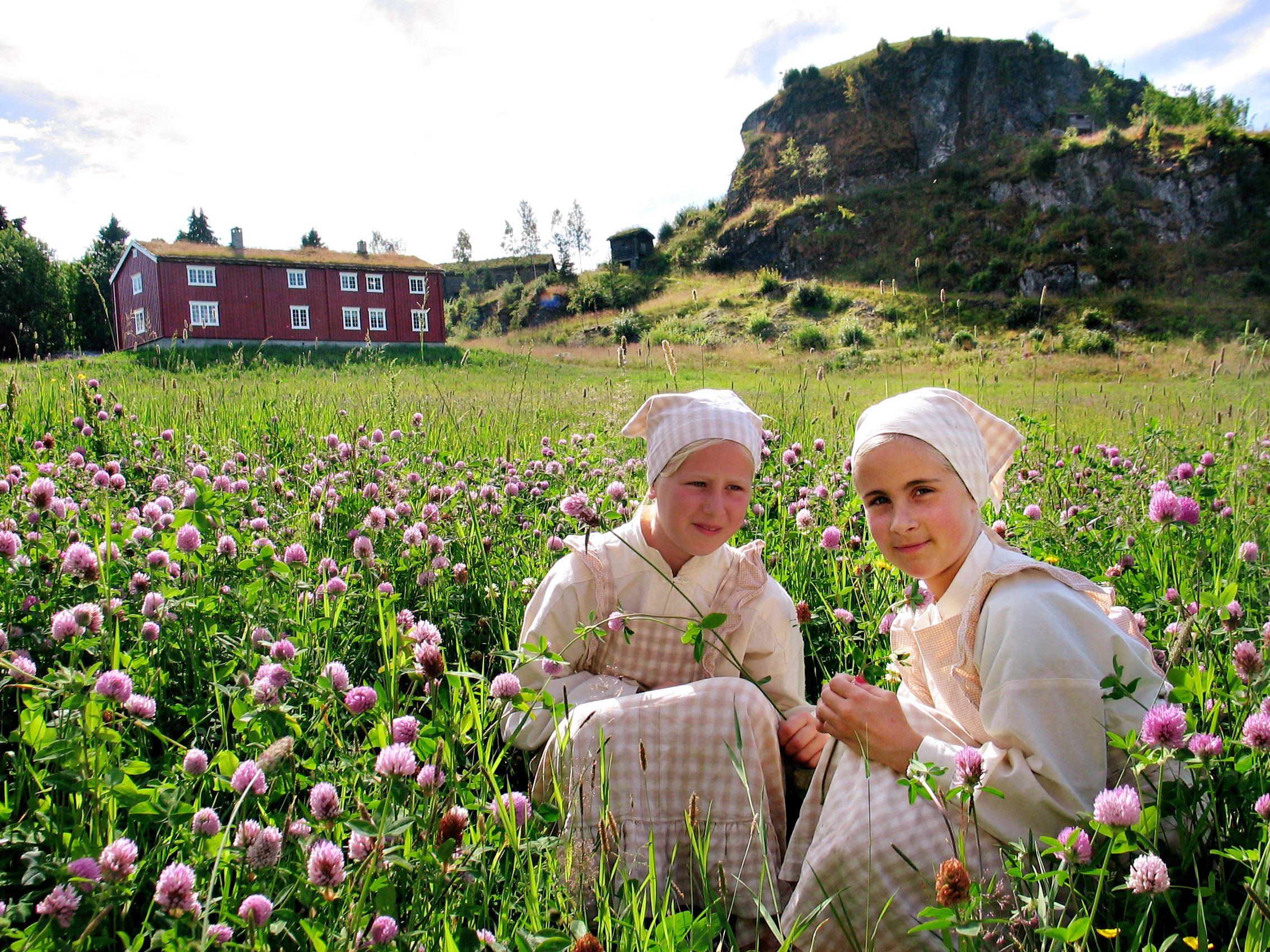Sverresborg Folkemuseum, Jenter i gresset med blomster i hendene ute på Sverresborg Trøndelag Folkemuseum