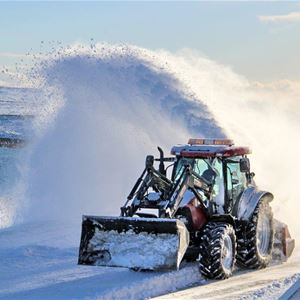 Traktor som freser sne.