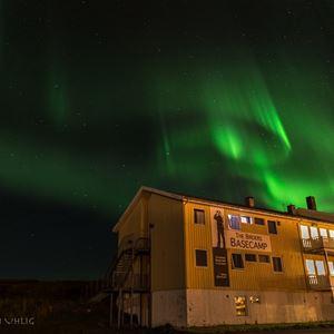Bilde av utsiden av Vadsø Fjordhotell. Tatt i mørke å viser nordlyset danse over himmelen.