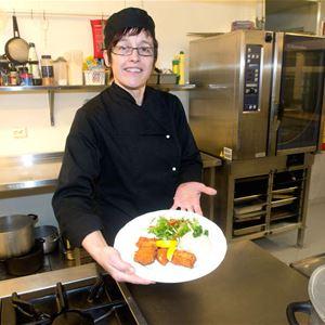 Her er Gunn - Marit Nilsen som er eier av Polar Hotell. Her sår hun på kjøkkenet å viser fram en fantastisk fiskerett på tallerkenen.