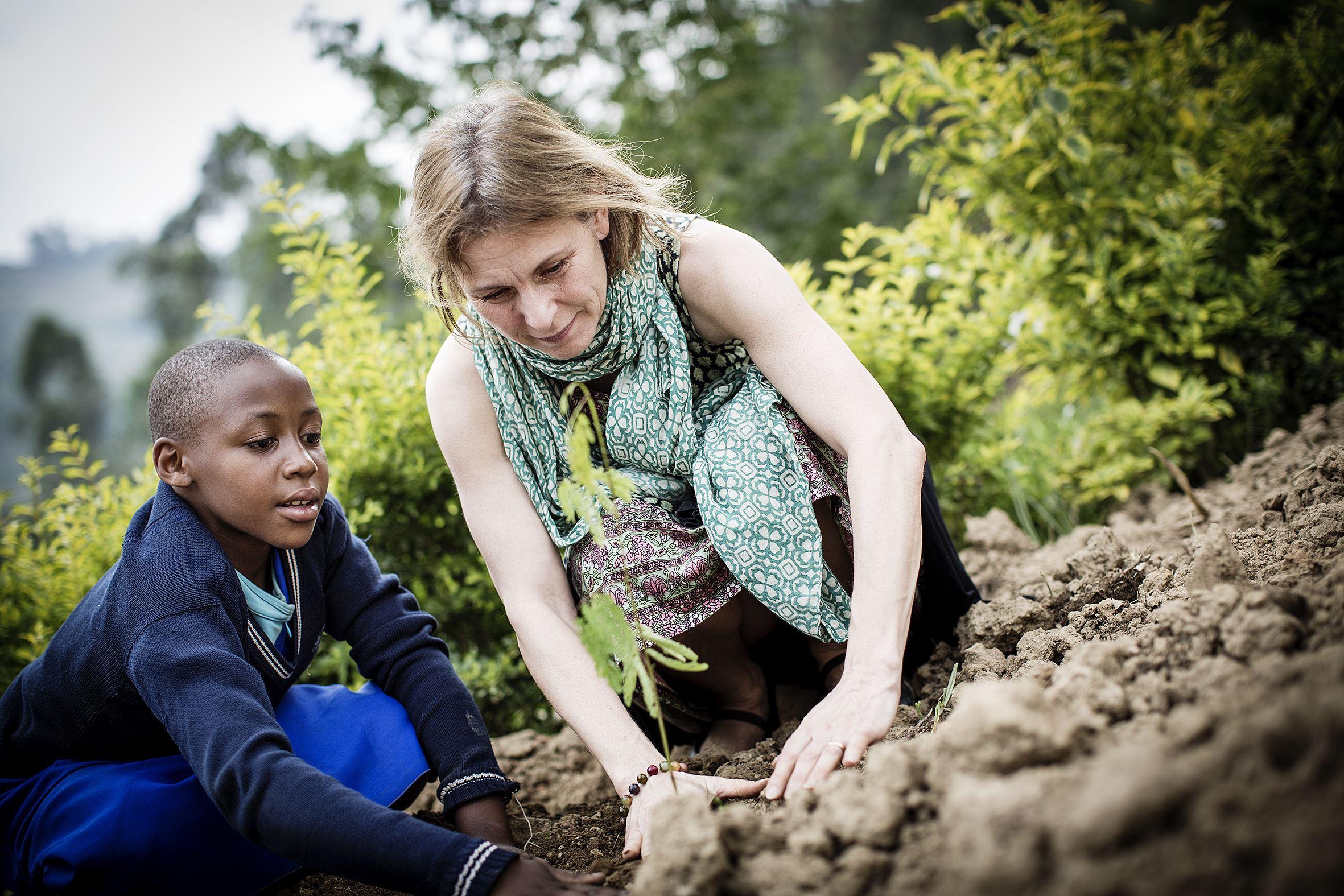 Marcus Lundstedt, Helen Sjöholm och Jolie Usanzituze planterar träd på Kininshyaskolans gård i Rwanda.