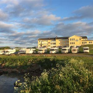 Bilde av utsiden av Vadsø Fjordhotell. Stor parkering til camping biler.