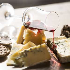 Various cheeses placed on a dish with biscuits and a glass of wine.