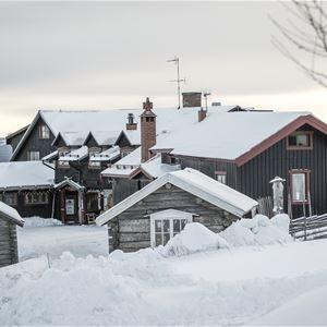 Hotellet med snö på taket och vitt på backen.