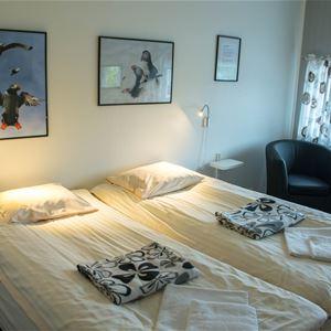 Dobbeltrommet på Polar hotell. Dobbelt seng oppreid, med en stol å et sofa bord ved siden av vinduet.