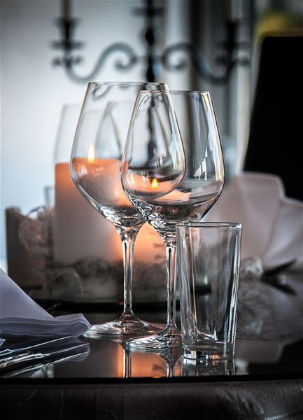 Bildet er tatt inne på restauranten på Polar Hotell. Nærbilde av dekket bord å levende lys.