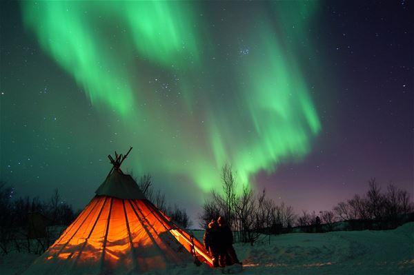 Nordlyset danser over himmelen, i nydelige farger i vinter mørket. Lavvo med lys.