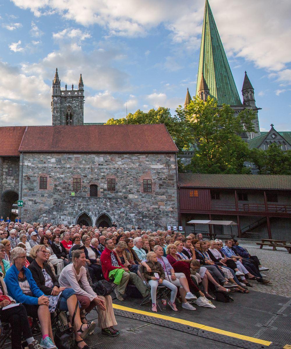 Olavsfestdagene,  © Olavsfestdagene, Bilde av mennesker som sitter i Erkebispegården under Olavsfestdagene