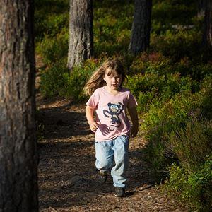 En flicka som springer på en skogstig.