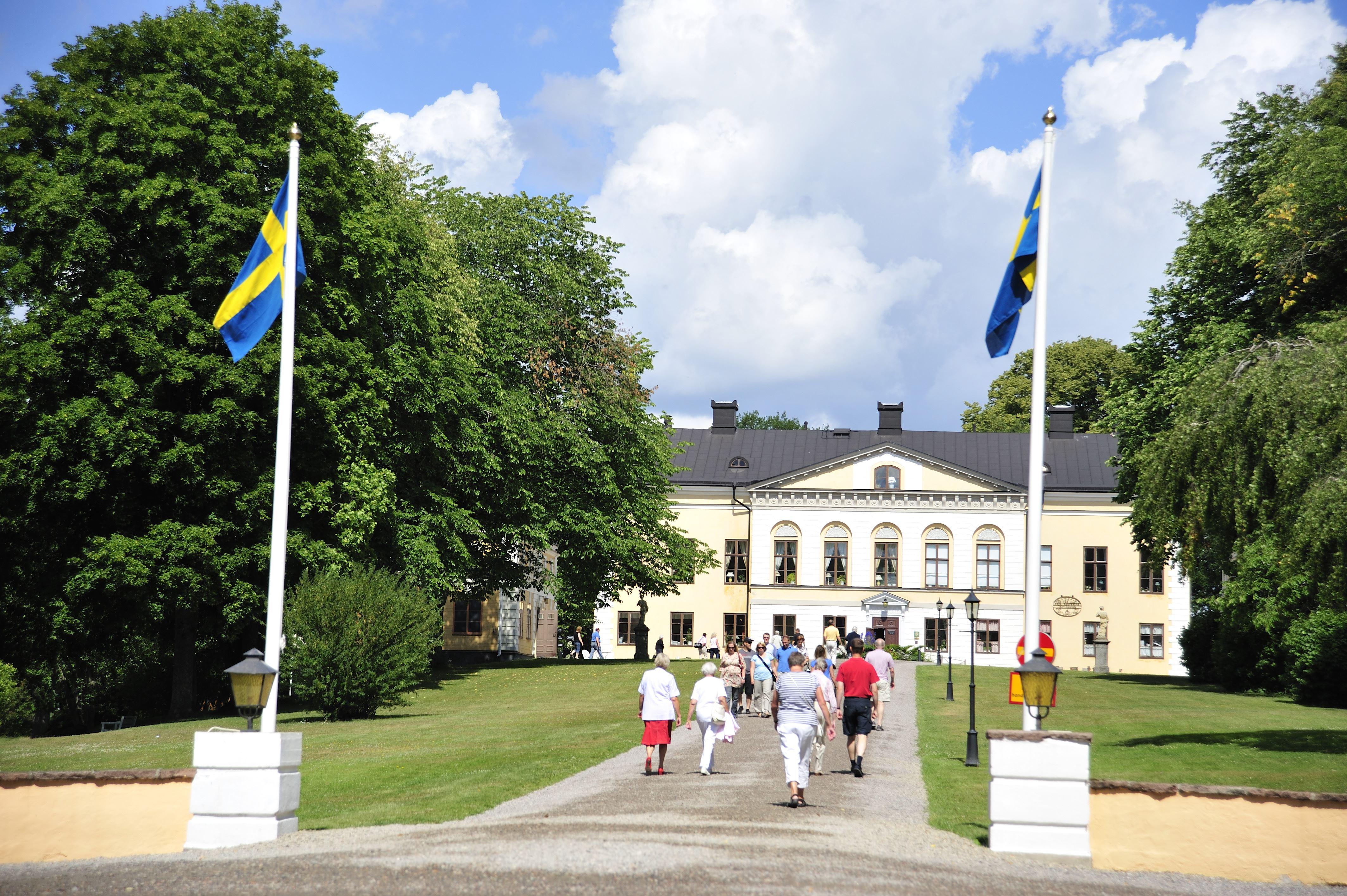 © Järnvägsmuseet, Entrén till Taxinge slott med hissade flaggor och solsken