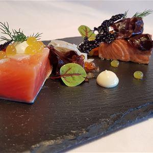 Tunn stenplatta med fisk och grönsaker.
