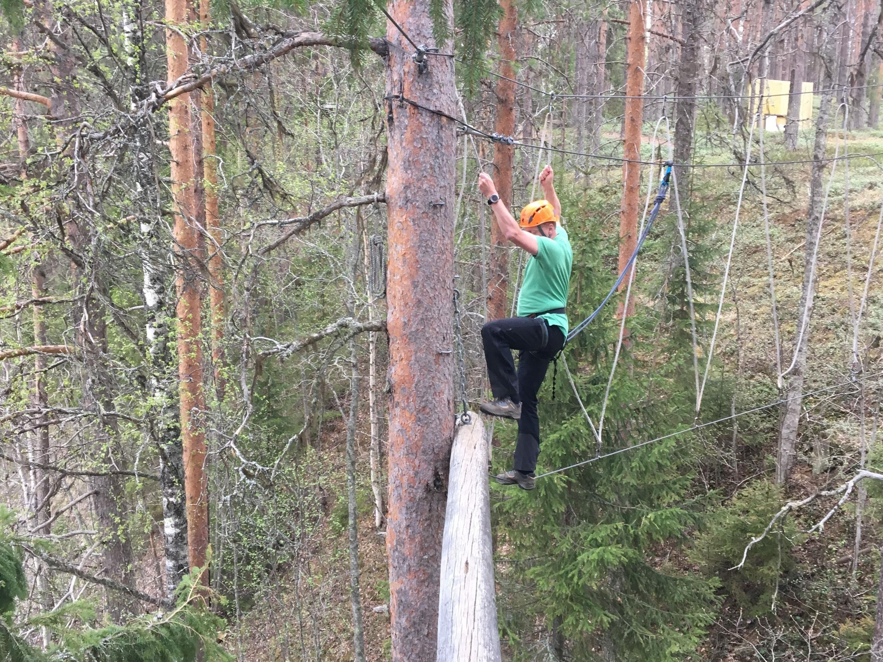 Man som går längs en lina bland träden