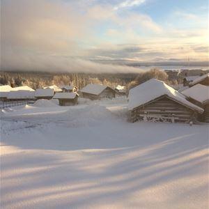 Vy över ett vintrigt Fryksås med gråa timmerstugor med snö på taken.