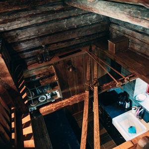 Vy från ett loft till nedervåningen i en stuga med synliga timmerväggar och ett par gamla träskidor.