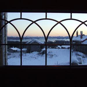 Utsikt över Fryksås genom ett blyinfattat fönster.