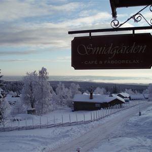 Siluett av Smidgårdens skylt mot en vintrig bakgrund från Fryksås.