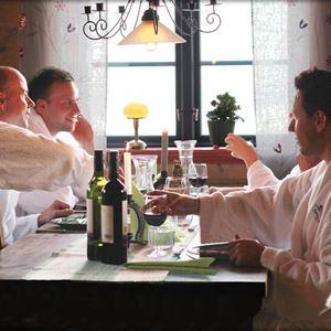 Fyra personer i vita badrockar sitter vid ett bord och dricker vin.