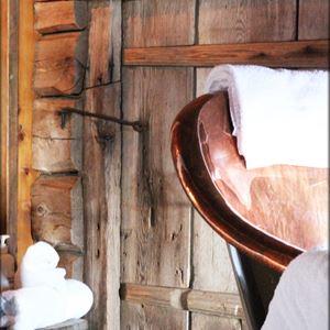 Detaljbild på vita badhanddukar mot grånad trädörr med hasp av smide.