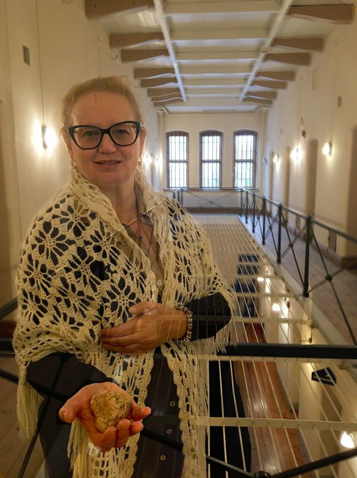 Desirée Kjellberg,  © sveriges fängelsemuseum, museipedagog Margit Söderström står i cellfängelset och håller fram en sten i ena handen.