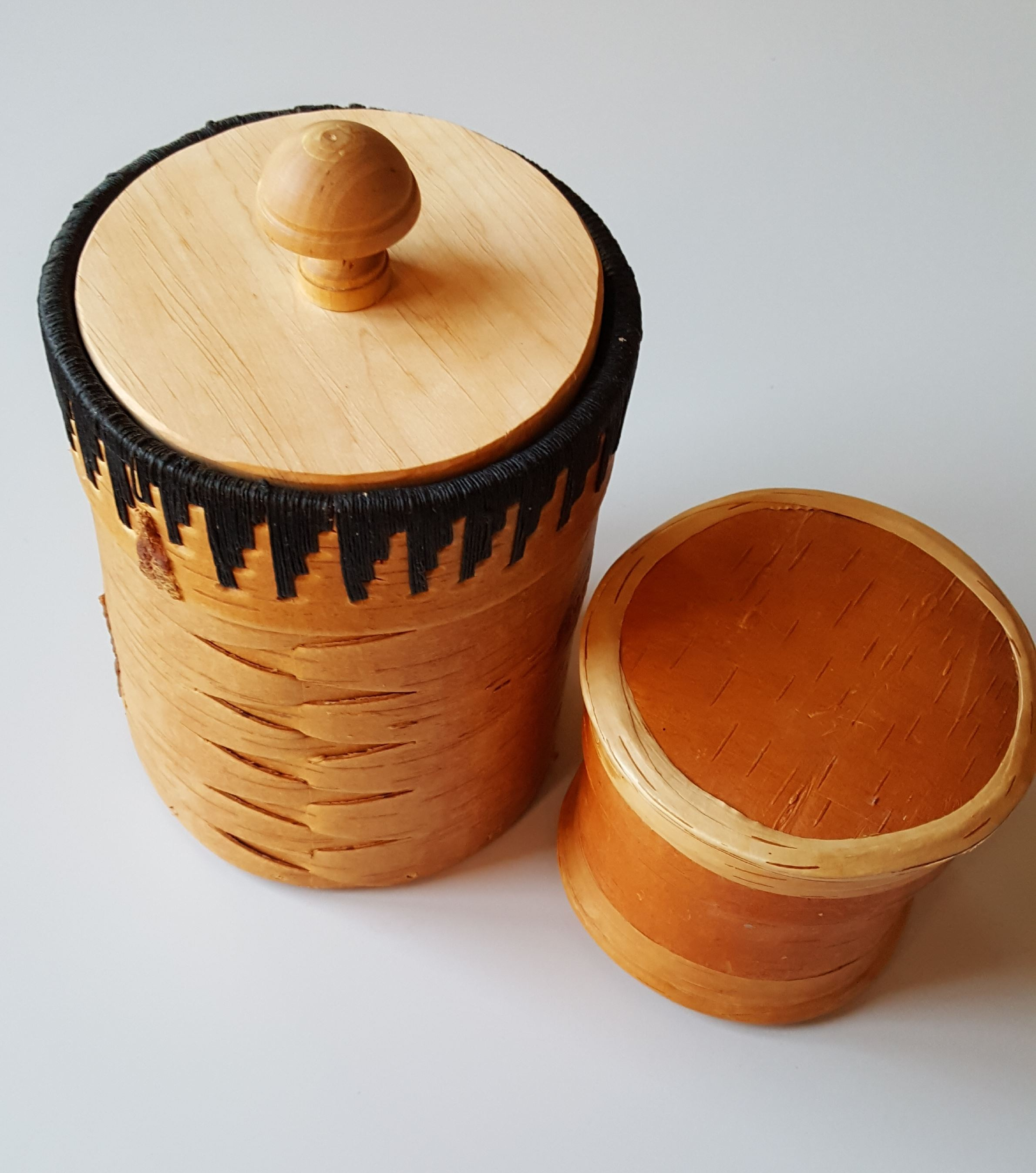 två burkar tillverkade av näver och med lock den ena burken har lock av trä den andra lock av näver