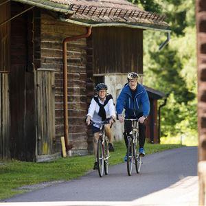 Ett cyklande par på en mindre väg bland äldre träbebyggelse.