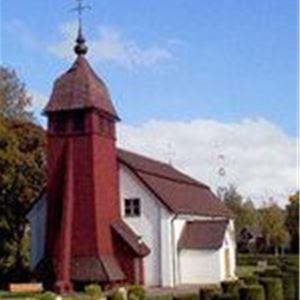 Djura kyrka med sitt röda torn mot den vita kyrkbyggnaden.