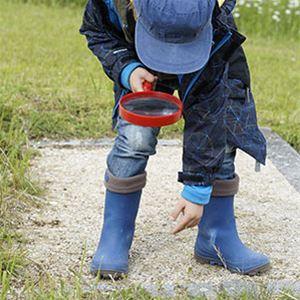 Ett barn med förstorningsglas som tittar på marken.