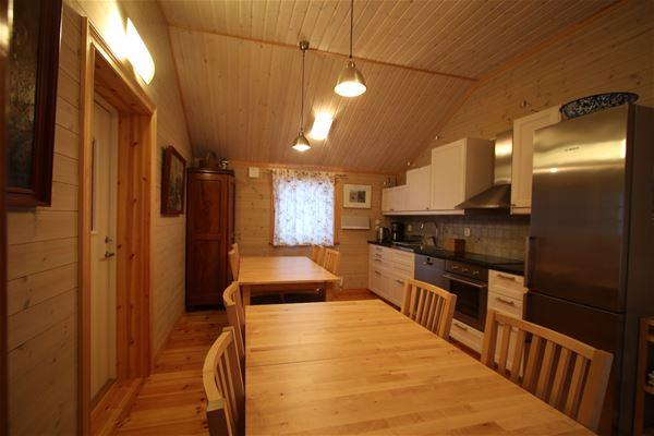 Köket med 2 stora matbord och stolar.