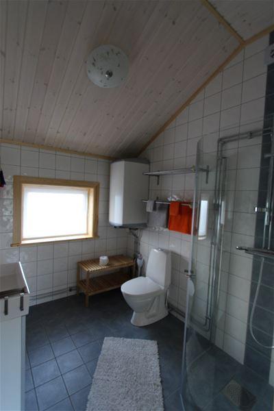 Badrum med vitt kakel och grått klinkers, wc, dusch med glasdörr, stort fönster.
