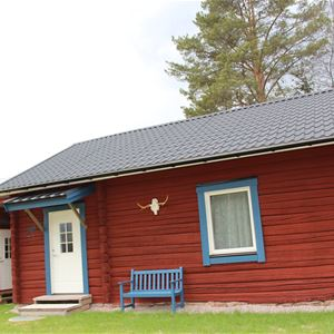 Red cabin with a blue bench in front of the cabin.