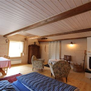 Large room with double bed,  open fire place, armchairs and a dining table.