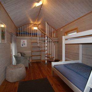 White bunkbed and a spiral stair to the loft.