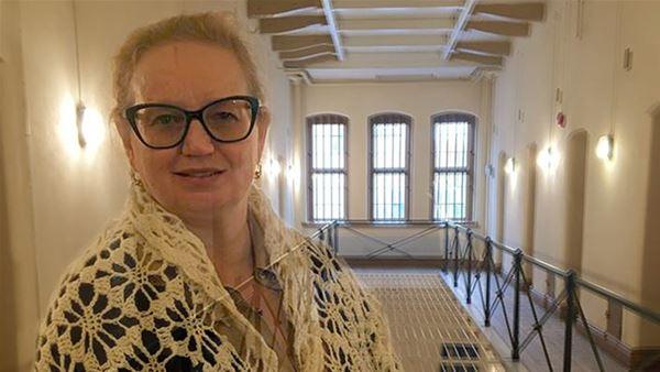 Sveriges Fängelsemuseum,  © Sveriges Fängelsemuseum, En kvinna står i ett mittskepp i ett cellfänglse