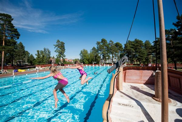 Children jumping into the outdoor pool.