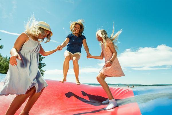 Three children jumping on a big air bag.
