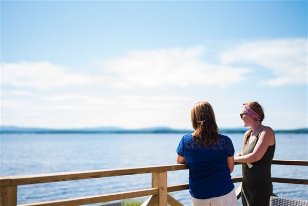 Two persons standing by the balcony railing looking at the view of the lake.