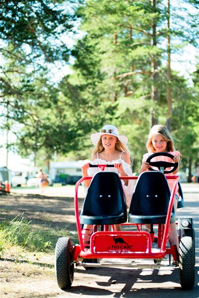 Two children on a red pedal car.