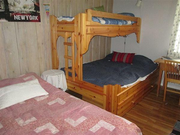 Sovrum med enkelsäng och en våningssäng med bredare underslaf.